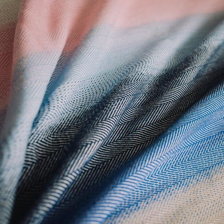 Didymos Lisca Northern Light. The colours of the warpdazzle like Northern Lights illuminating the northern night skies. On an organic cotton warp displaying all hues of blue from light to dark blended with natural white and pink, the raw white weft yarns set their highlight to this captivating colour combination.