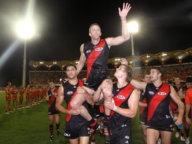 Dustin Fletcher is seen here chaired off the ground after the match by Paddy Ryder and Michael Hurley as the Gold Coast form a guard of honour in the background to mark their respect for the Essendon game breaker!