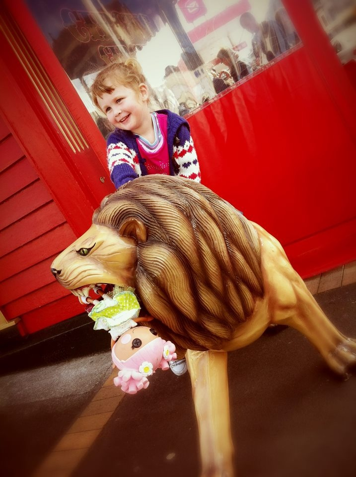 My daughter riding (and feeding) a lion at Circus Circus cafe in Auckland, New Zealand