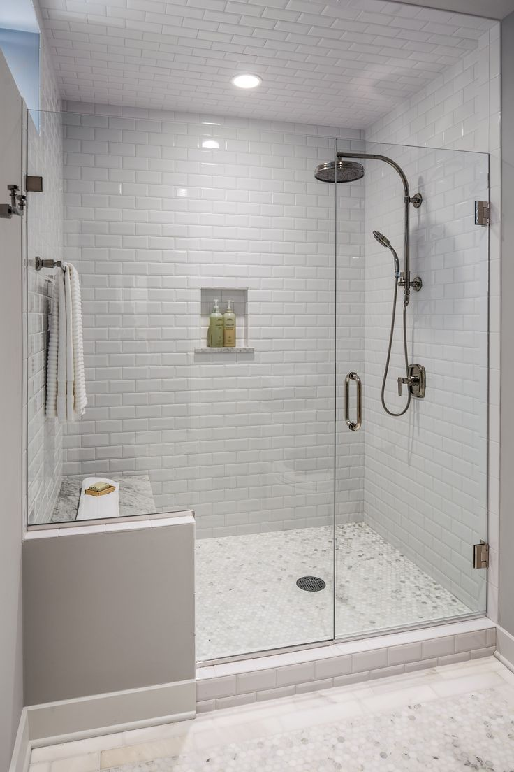 The guest bath had a shower area that was dated and confining. A new frameless glass shower is roomier and allows in natural light. A built-in bench, marble floors and glazed subway tile walls and ceiling finish off this suite. #ShowerHeads
