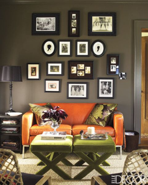 Who says family photos can't be stylish? Living room wall covered in smartly framed photos really pops with the addition of orange couch and green benches acting as a coffee table.