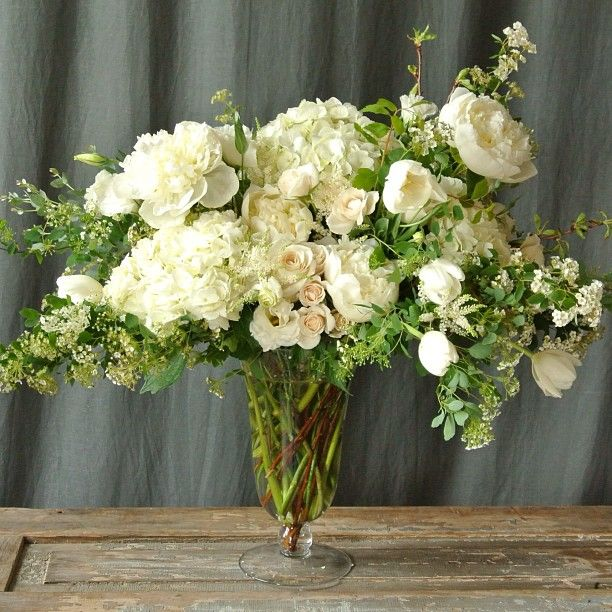 White and green, large spring arrangement in a clear trumpet vase. Designed by Sullivan Owen