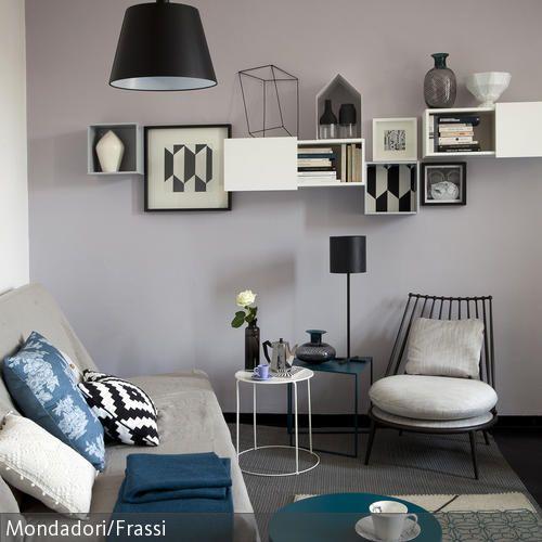 Gekonnt kombiniert: Möbel im skandinavischen Design in Schwarz und Weiß, dazu Regalkästen und Bilder mit grafischen Mustern an der Wand. Das Sofa mit  …