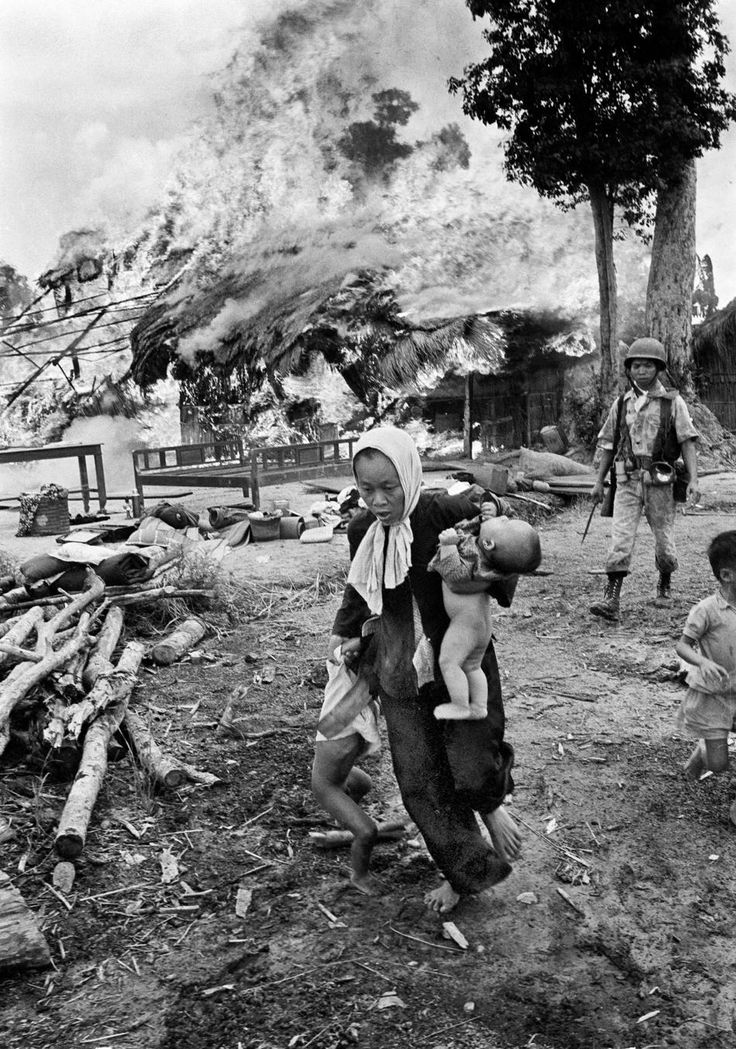 Vietnam War:  South Vietnamese villager scurries as her village is burning in the background during a South Vietnamese Army anti-guerrilla patrol. She's is trying to remove a baby and a toddler from the scene as a South Vietnamese soldier approaches from behind holding a bayonet. Vietnamese villagers formed the majority of victims of the war.