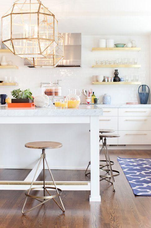 Bright and modern kitchen pops of bold color and beautiful brass and gold accents in the geometric pendant lamps, open shelving and drawer pulls.
