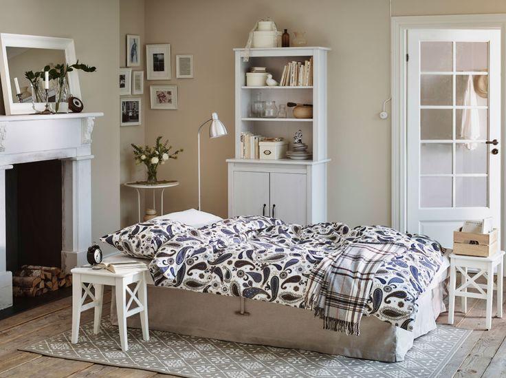 ホリデーコテージのリビングルームにベージュのソファベッド、ベッドリネンはブルーとホワイト。ベッドサイドテーブルにはホワイトのスツールを使い、ハイキャビネットも置いて