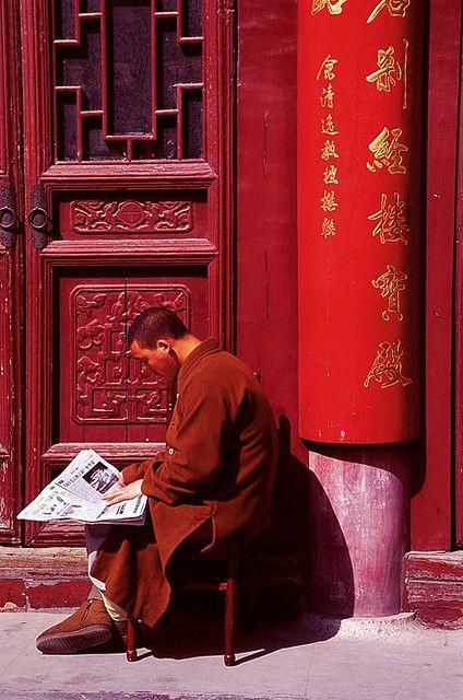 All red - A Budhist monk reading the latest chinese news. Nanjing, Jiangsu China