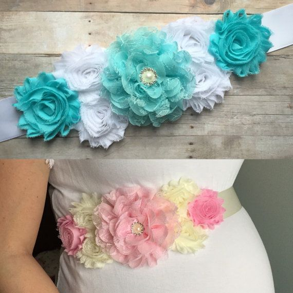 Your choice of pink or blue maternity sash. This beautiful Maternity/Belly sash is a MUST for your maternity pictures or your baby shower!!! This sash features an assortment of flowers of all different sizes & a rhinestone center. Flowers are attached to a 1.5 wide satin ribbon. Ribbon length measures 2 yards-- this sash is one size fits all!  Pink Sash- Pink & ivory flowers on an ivory satin ribbon, center rhinestone embellishment  Blue Sash- Aqua blue & white flowers on white satin sash…