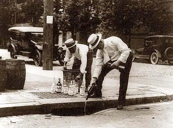 This photograph was taken in 1920, back in the time of prohibition. The picture shows city officials pouring bootleg whiskey down the storm drain