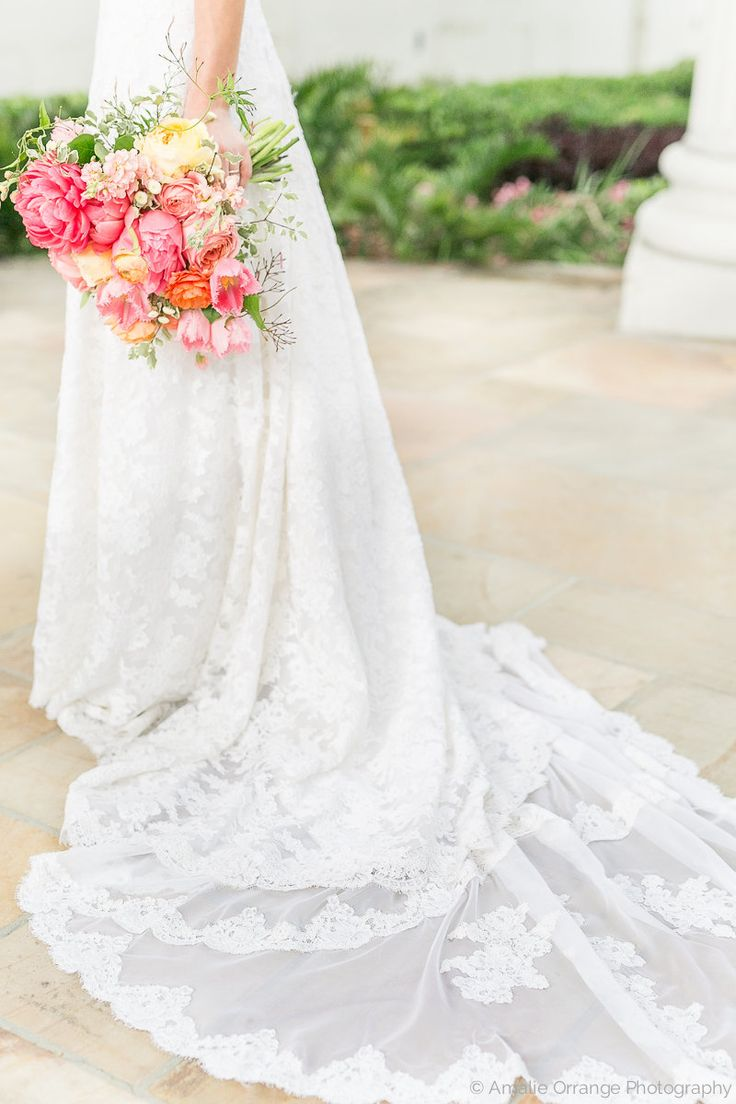 in a stunning lace wedding gown with a train to die for, the bride holds her loose bridal bouquet of spring flowers including coral charm peony, romantic antique garden rose, caramel antique garden rose, peach stock, pink fringe tulip, peach ranunculus, white majolik spray rose, white button chamomile, variegated italian pittosporum& jasmine vine wrapped in cream satin ribbon.