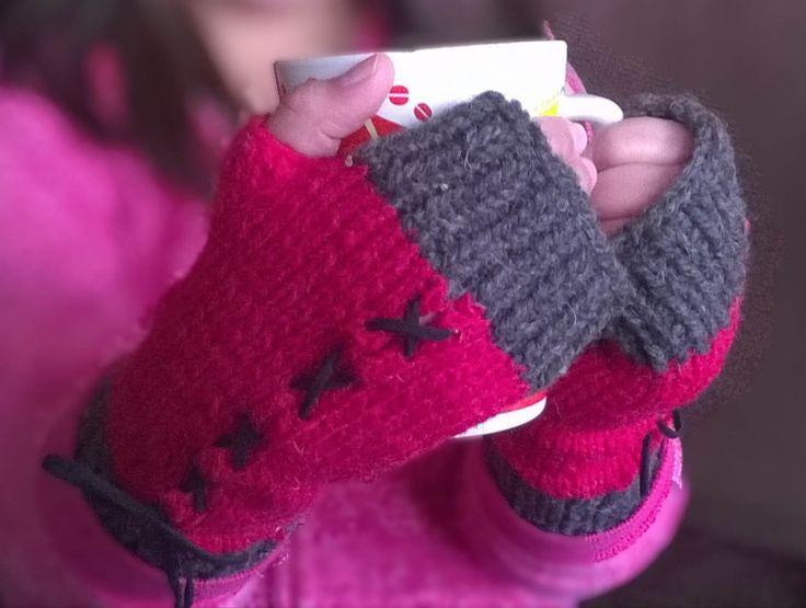 Mitones tejidos en dos colores, en lana cien por ciento natural, con una cinta de gamuza como adorno.