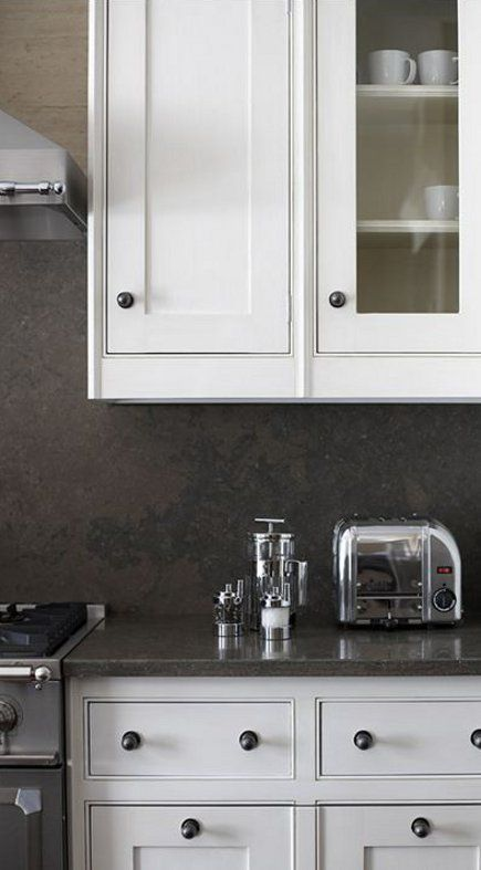 the dark taupe limestone look is used for counters and matched by a honed texture backsplash. Black Bedroom Furniture Sets. Home Design Ideas
