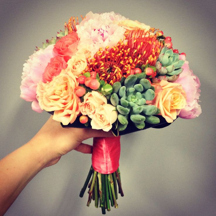 Bridal bouquet for a coral wedding - a mixture of roses, spray roses, pincushion protea, succulents, hypericum berries and peonies.