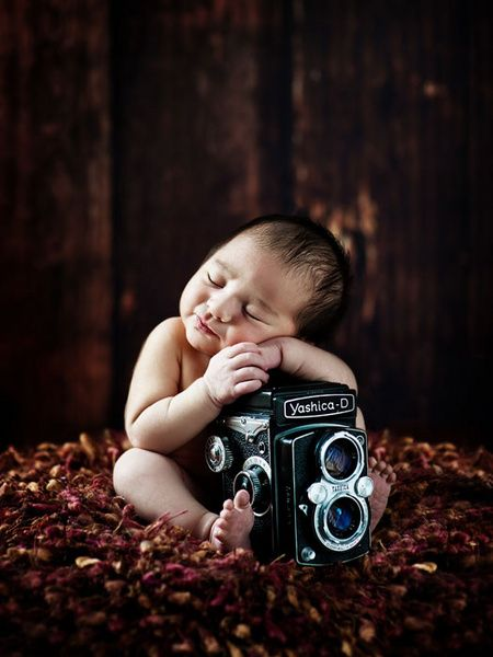 This baby thinks some of the poses they use today are so bad, he is gonna take his own damn photo.