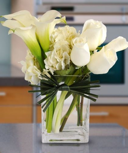 Reflections - This dazzling design includes hydrangea, calla lilies and roses and is accented with a bear grass bow looped around the square vase.