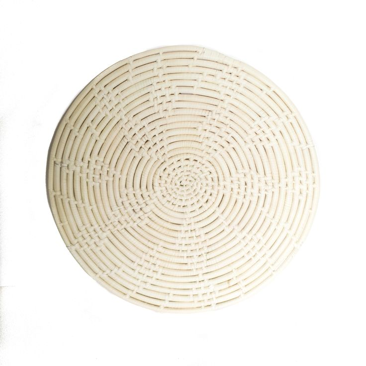 """Hot pad and elegant table decoration all in one. This circular trivet is made out of the same woven material as our baskets but is the perfect centerpiece for any table. We partner with 2nd Story Goods in Haiti which provides jobs to local artisans which pay 3-4 times the minimum wage.  Made in Haiti Hand woven Approximately 12"""" round"""