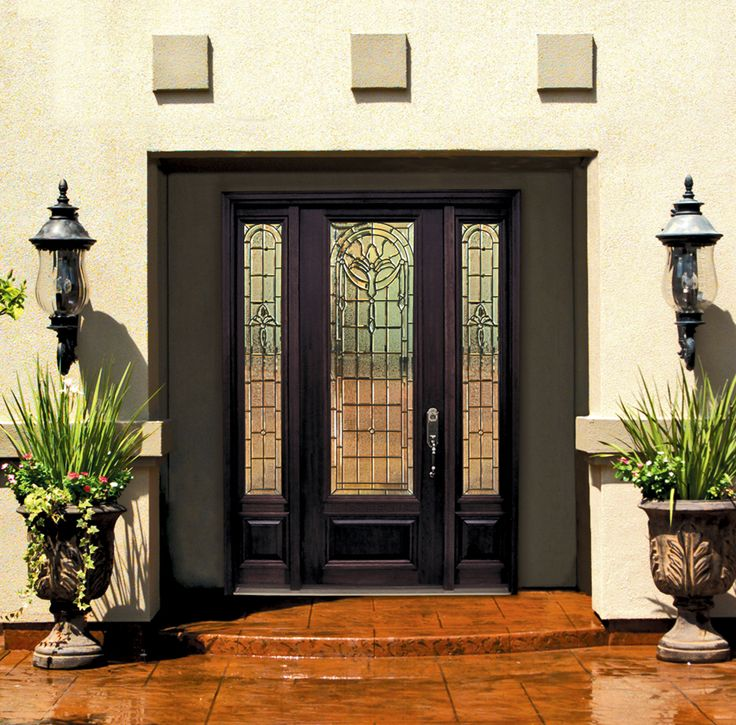 Mediterranean architecture complemented by a beautiful decorative glass door with sidelites in GlassCraft's unique Palmetto design.