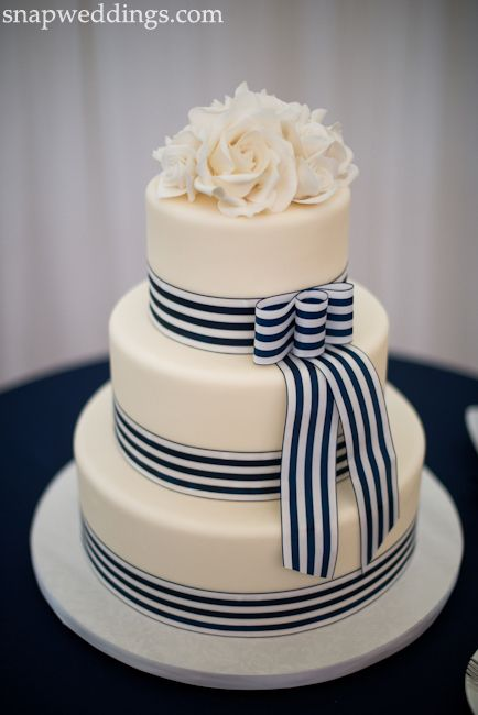 Three tier round cake with simple white flower topper finished with a white and navy ribbon