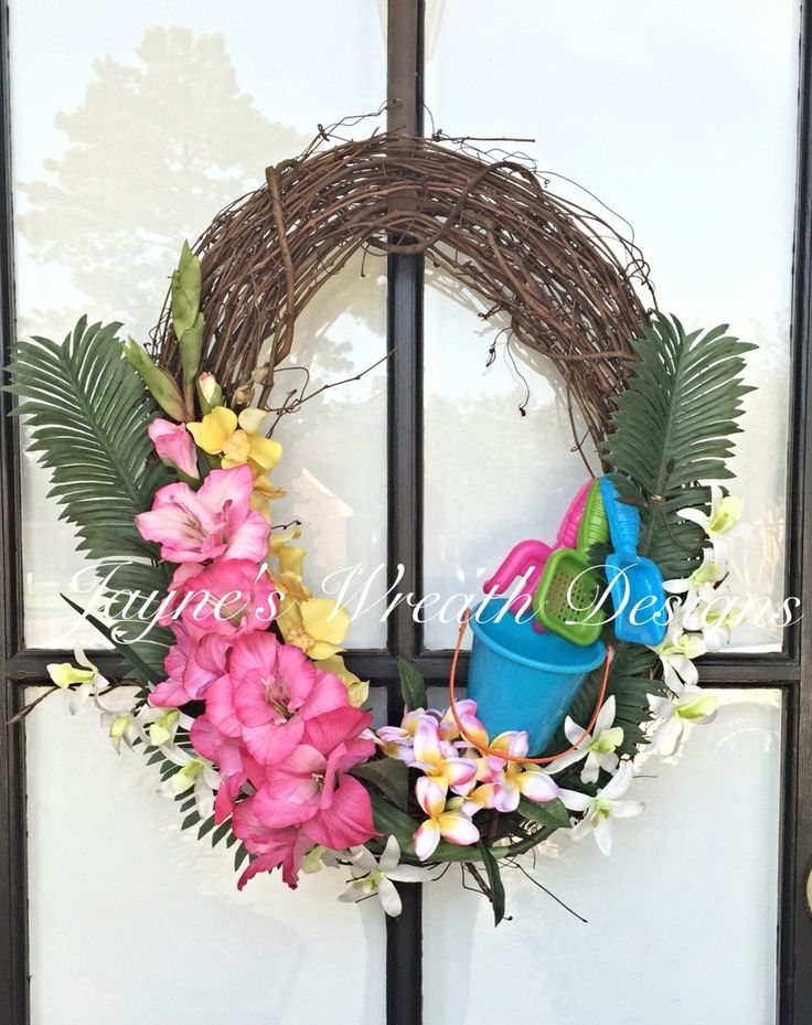 Oval Summer Grapevine Wreath with Tropical Flowers, Shovels and Pail. This is a great wreath for a tropical beach theme. By Jayne's wreath designs on fb and Instagram