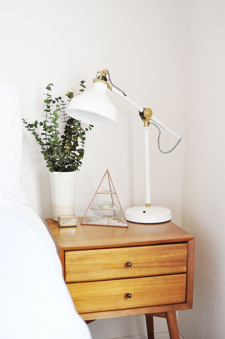 It's hard to keep a bedside table looking minimal but this is a great example of how to do it - white angled lamp, small indoor plant and golden terrarium. Simple but stylish.