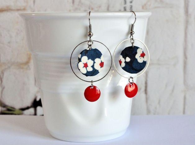 Boucles d'oreilles Liberty  Un bijou original et coloré, en tissu Liberty bleu à fleurs blanches.  Bijou orné d'un anneau argenté, d'un pendentif Liberty et d'une pampille rouge.  Des boucles...