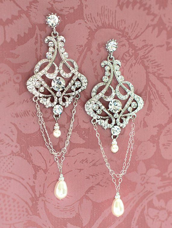 Vintage, 1920s style chandelier bridal earrings combine an ornate rhinestone setting with pearl drops and dangling chain. The earrings are set on a surgical steel post backing.The earrings are high quality using Swarovski rhinestone encrusted alloy settings.  ***WEIGHT: These are high quality metal alloy and Swarovski encrusted earrings that are heavier than average size earrings due to their size. One earrings weighs approx. 0.75 oz (21 kg)  Measurements / Details: - 4 3/8 in lengt…