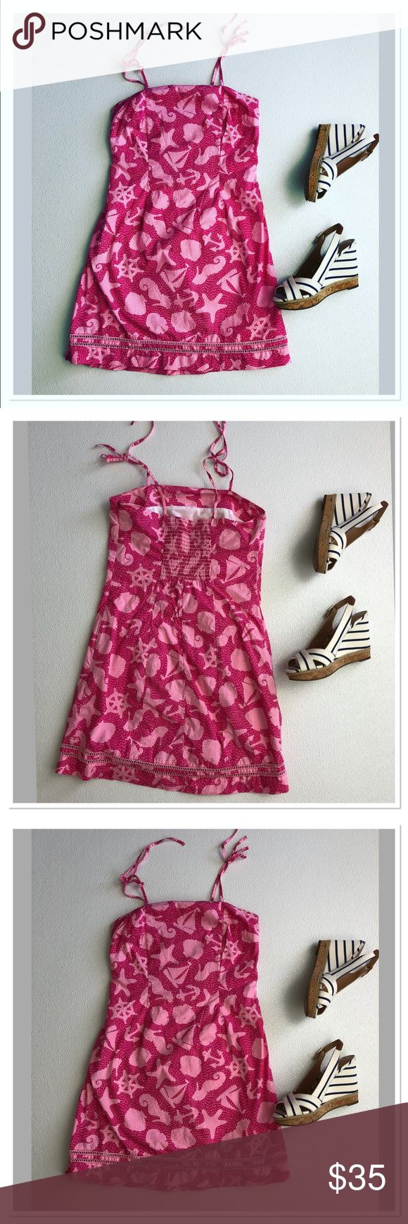 "Lilly Pulitzer seashells tie spaghetti strap dress Lilly Pulitzer seashell nautical print tie spaghetti strap eyelet dress made of 100% cotton. Fully lined dress featuring adjustable tie straps, elastic back side zip closure eyelet hemline. Bright pink summer pattern. Little spots as pictured, very small and barely noticeable due to a busy print, price reflects. Otherwise, great condition. Cute dress, cocktail dress, graduation dress. Size 6  Pit to pit: 16"" Length: 33"" Waist: 14,5"" Lilly…"