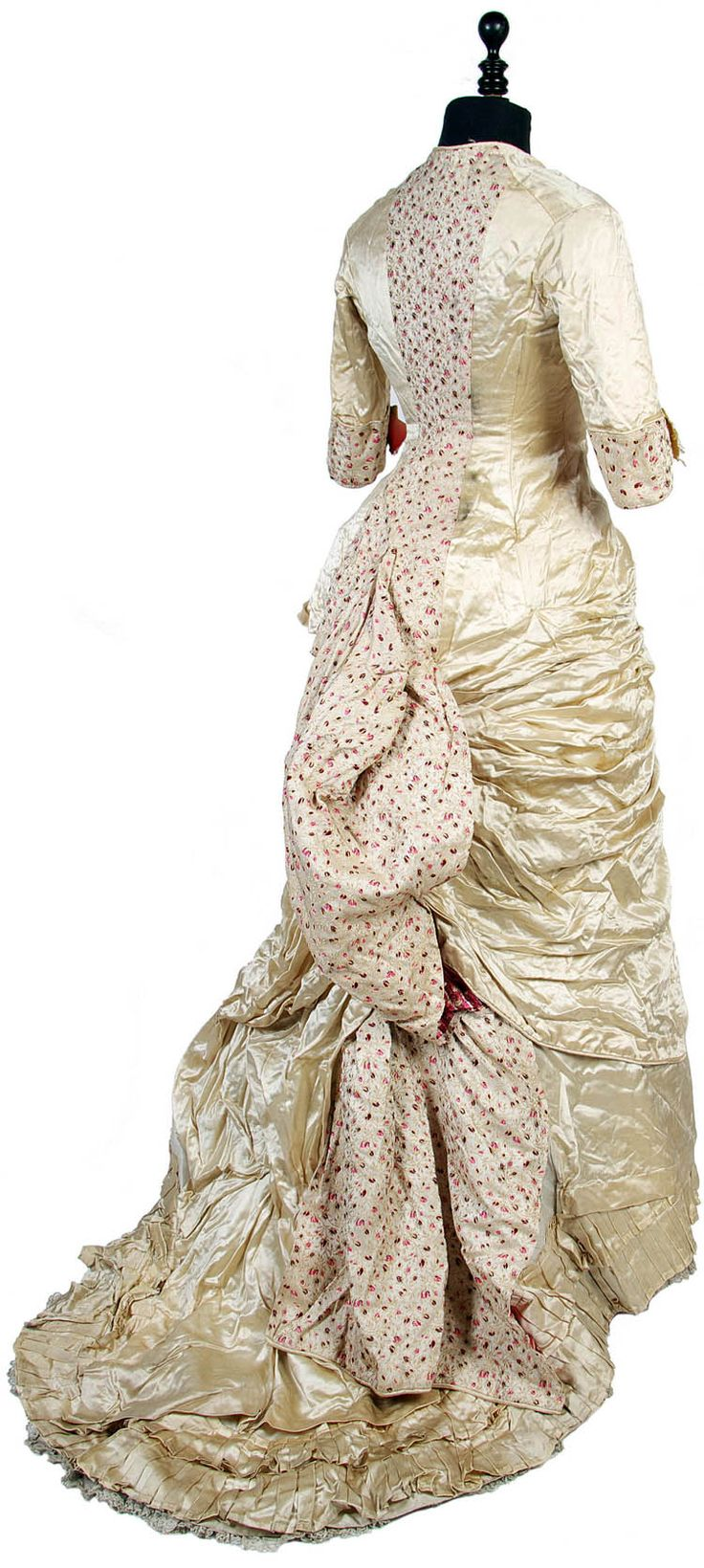 An 1870s cream silk satin princess-line dress with rosebud brocade inserts. Deep swags over the hips and large bustle; trimmed with pink satin ribbon. Bonham's