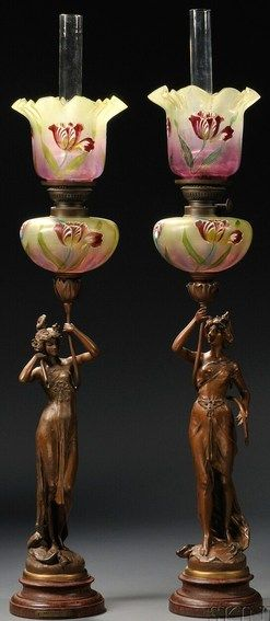 lighting, France, Pair of Art Nouveau figural spelter oil lamps with glass shades, early 20th century, the glass shades polychrome enameled with tulips above figures. Titled Nenuphars and Pavots, each cast as astanding woman in a diaphanous dress, on circular stepped and marbleized bases