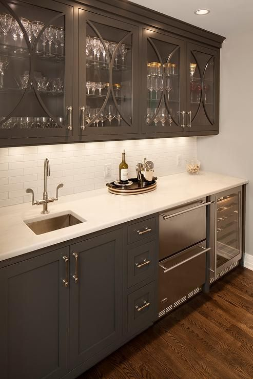 Gray butler's pantry boasts glass front upper cabinets with gray eclipse trim moldings and gray ...