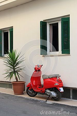 Red scooter parked beside wall of a house Hersonissos, Crete, Greece.