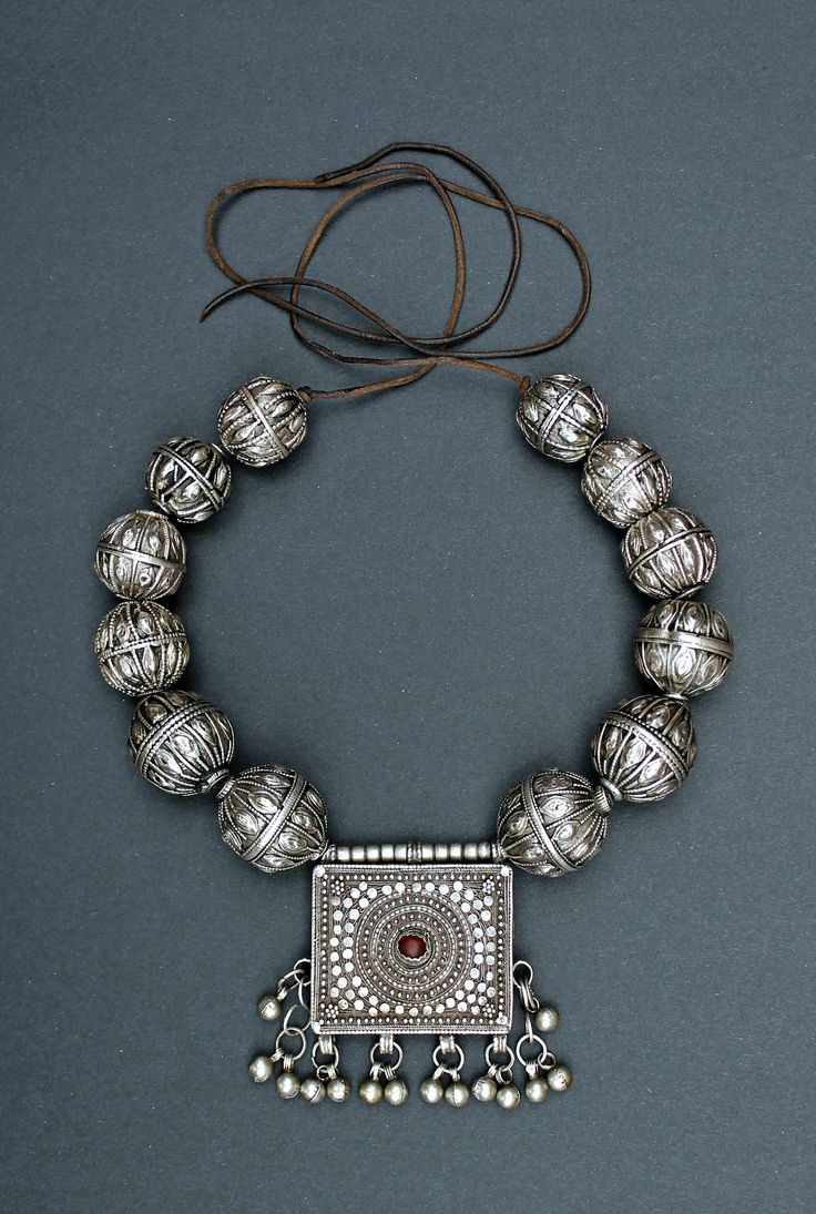 "An old silver necklace from Yemen. With a ""mahfaza"" amulet box, and silver beads each bearing the signature of the smith. From northern Yemen, probably Sanaa or Saada, and early 20th century"