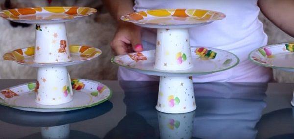 подставки для сладостей  Из цветных пластиковых стаканчиков и тарелок можно соорудить суперэтажерки для сладостей. Достаточно просто склеить стаканчики и тарелки между собой