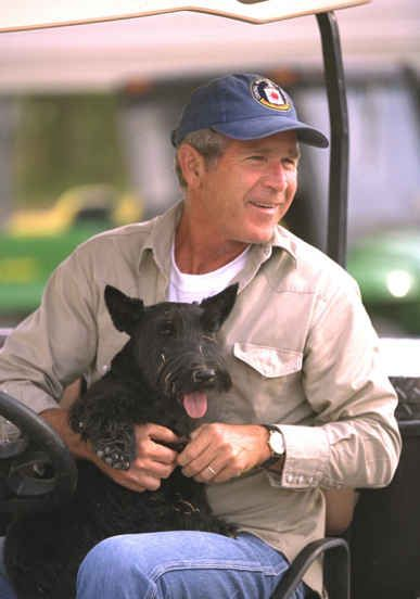 George W. Bush chilling with his dog Barney in a golf cart