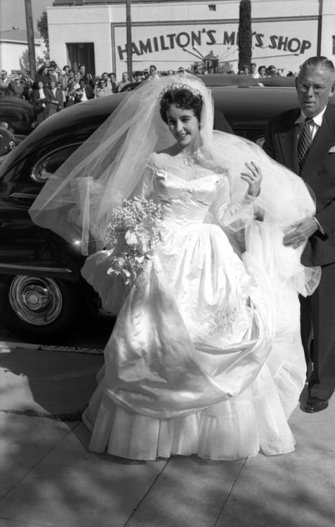 "Unpublished Life Magazine Photo: Just 18 years old, Elizabeth Taylor arrives to marry hotel heir Conrad ""Nicky"" Hilton at the Bel-Air Country Club. This was the first of her eight marriages, and for the occasion she wore a gown given to her by MGM Studios."