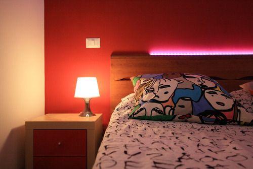 Dettaglio del letto con parete di fondo dai colori vivaci e illuminazione a led rgb
