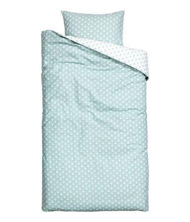 Et sengesett i fintrådet bomullskvalitet med trykt mønster. Dynetrekket knappes nederst med skjulte trykk-knapper i metall. Et putevar. 30s-garn. Trådtetthet 144.