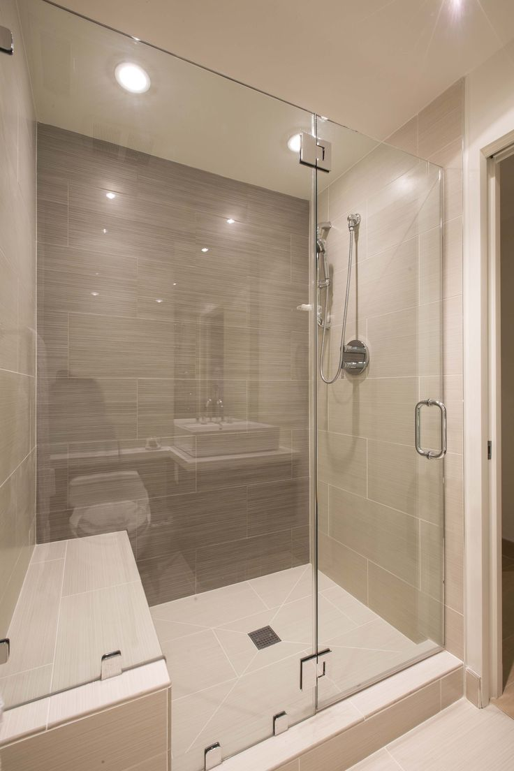 This modern bathroom has a large glass-enclosed shower in tile. The shower stall includes a bench and recessed lighting. Designed by http://www.formaonline.com/home/index.shtml
