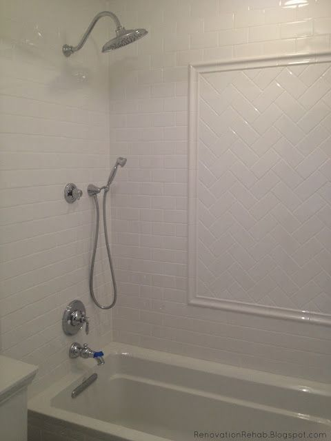 White Subway tile shower with herringbone subway t…