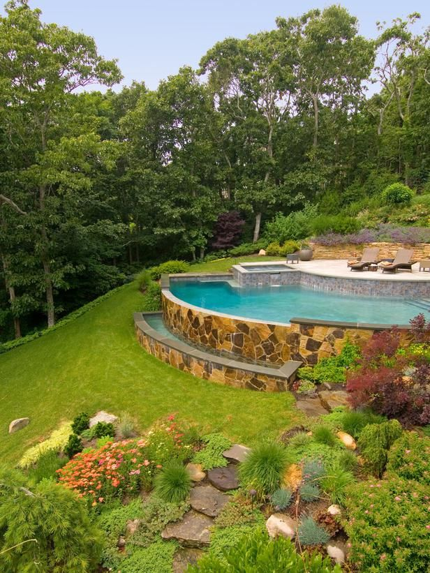 Stunning Infinity Pool: An arc-shaped pool with a spa is built into the hillside, where cascading water gently rolls over the Misty Rose flagstone veneered pool wall, producing a calming effect. The infinity edge is designed to spill into a raised trough that doubles as a sitting area and water sculpture. From HGTV.com's Garden Galleries