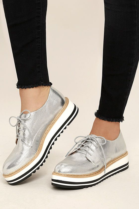 """All the cool girls know that the Steve Madden Vassar Silver Platform Sneakers are where it's at! These unique loafer-inspired sneakers have a metallic perforated upper, grey laces, and tan top-stitched welt. White and black 1.5"""" rubber sole."""