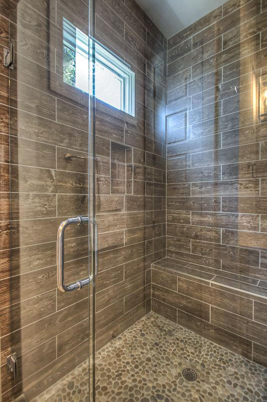 Faux wood plank shower wall tile and pebble shower floor tile