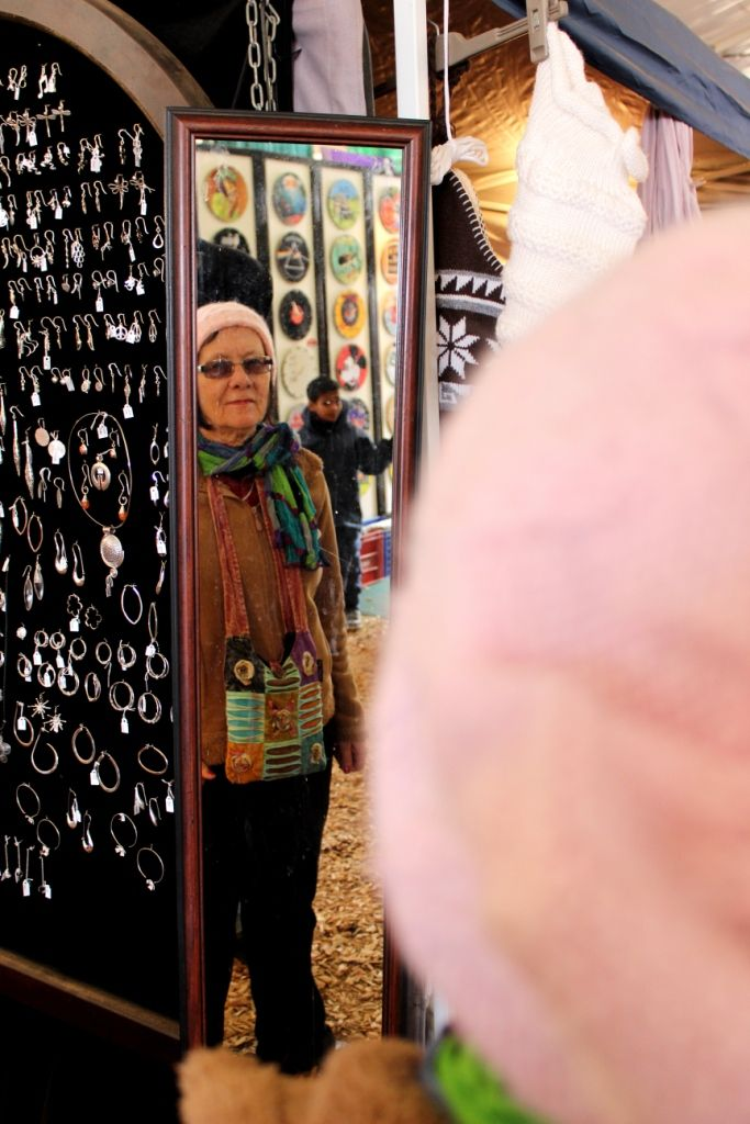 Woman from the Northern Cape tries on a hat and examines her reflection in the mirror