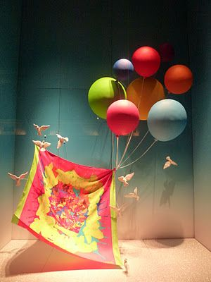 "A vitrine da Hermès, em Paris, usando balões e pássaros como ponto chave para dar a impressão de que os lenços - carro chefe da marca - são leves, suaves e delicados. | Hermès's window display in Paris shows baloons and birds holding a scarf to make it feel like it's soft and delicate, and give this ""fairytail"" look. Hermès is a reference in visual merchandising and retail design."