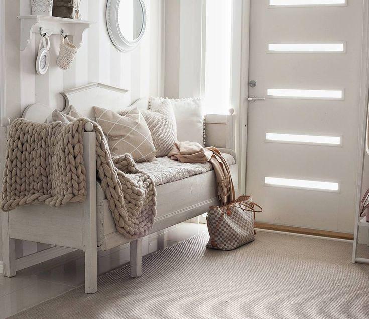 Puusohva tyynyineen ja viltteineen tuo kodikasta tunnelmaa eteiseen ja toivottaa vieraat lämpimästi tervetulleiksi.