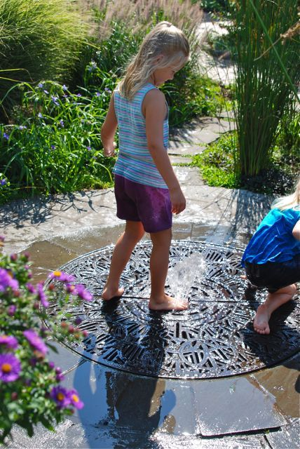 A bubbling fountain in the middle of a decorative metal grate. My kids love to play with this small, simple water feature for hours! I think it would be a fun design to include in a home garden.