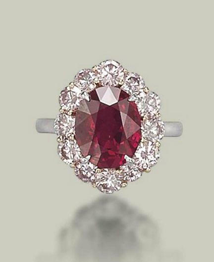 AN EXCEPTIONAL RUBY AND COLOURED DIAMOND RING  Set with an oval-shaped ruby, weighing approximately 5.09 carats, to the pink diamond surround, mounted in platinum and gold