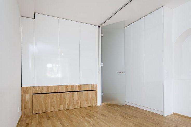 """Skříně se díky bílé barvě v prostoru """"ztrácejí"""". Domácí kancelář je z druhé strany na pódiu."""