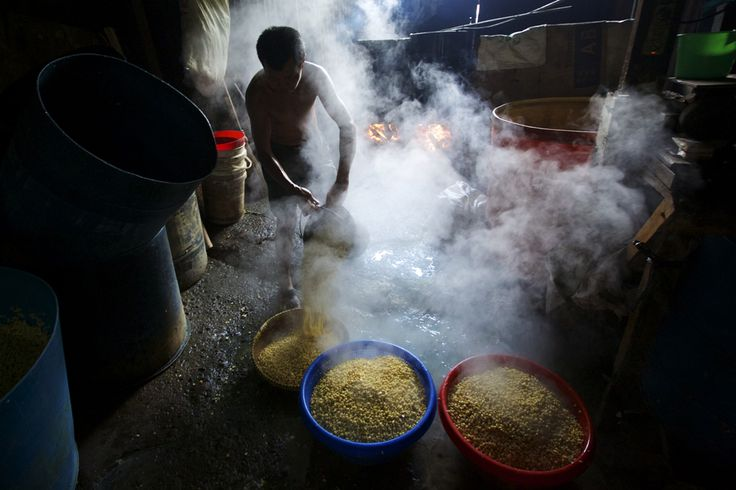 A worker drains soybeans after they have been boiled at a small tempeh factory on July 12 in Jakarta, Indonesia. Tempeh is an Indonesian staple made from fermented soybeans. The Indonesian government has said that it will increase food imports during the Ramadan fasting month to reduce inflation caused by increased food consumption during the month leading up to and during the Eid Al Fitr holiday marking the end of the fasting month. (Ed Wray/Getty Images)