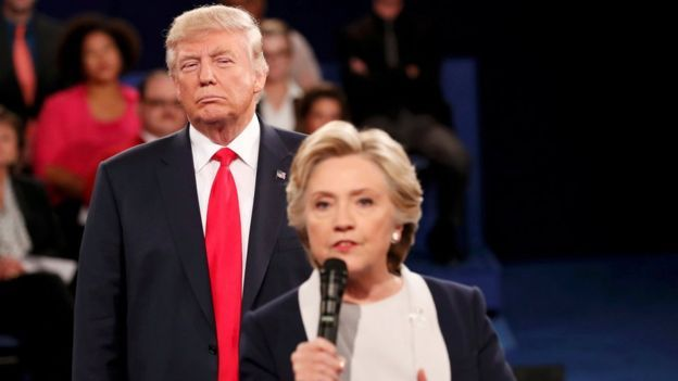 "LOOK AT THE MALEVOLENT LOOK ON TRUMP""S FACE . Republican US presidential nominee Donald Trump listens as Democratic nominee Hillary Clinton answers a question from the audience during their presidential town hall debate in Missouri on 9 October"